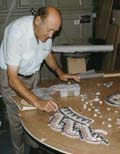[My father testing the marble pieces for size on his design]